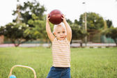 Little boy holding a ball above his head — Stockfoto