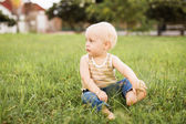Baby boy sitting on the green grass — Stock Photo