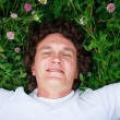 A young man lies on the grass — Stock Photo