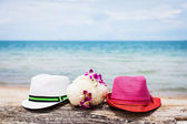 Two hats and flowers on a beach — Stock Photo
