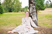 Woman in a meadow talking to a birch tree — Stock Photo