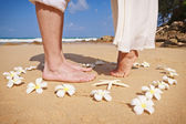 Male and female feet in the heart of flowers — Stock Photo