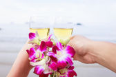 Glasses and flowers in hands — Stock Photo