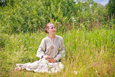 Woman sitting on a meadow — Stock Photo