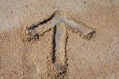 Arrow drawn on a beach — Stock Photo