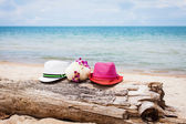 Two hats and flowers on a beach — Стоковое фото