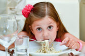 Cute girl eating pasta — Stock Photo