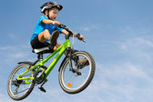Boy jumping on bike — Stock Photo