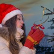Girl blowing on christmass decoration — Stock Photo