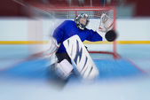 Young hockey goalie catching a flying puck — Stock Photo