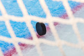 Hockey puck through goal net — Stock Photo