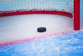 Hockey puck crossing goal line — Stock Photo