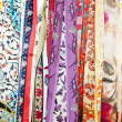 Row of silk products hanging on a market stall — Stock Photo