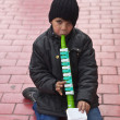 STANBUL, TURKEY - MARCH 9, 2014 : Little kid playing a plastic flute in the street, collecting money from people walking by. Working kids issue is an important problem in Istanbul, taken on March 9 — Stock Photo #42302731