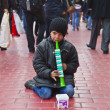 STANBUL, TURKEY - MARCH 9, 2014 : Little kid playing a plastic flute in the street, collecting money from people walking by. Working kids issue is an important problem in Istanbul, taken on March 9 — Stock Photo #42302771