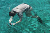 Woman photographer diving into water of Red sea — Stockfoto