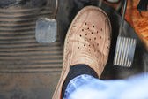 Mans feet pushing on the accelerator of automobile — Stock Photo