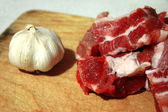 Fresh meat and fresh garlic laying on the kitchen desk — Stockfoto