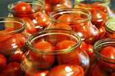 Tasty tomatoes ready to canned in glass jar — Stock Photo
