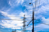 Electric power transmission under white cirrus clouds — Stock Photo