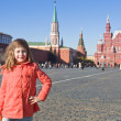 Stock Photo: Girl in red coat on Red Square in Moscow