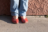 Legs in blue jeans and red shoes — Stockfoto
