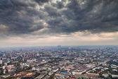 Dark grey autumn clouds under big city — Stock Photo
