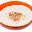 Oat porridge with cinnamon in orange bow — ストック写真