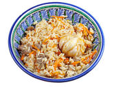 Traditional asian pilaf with garlic bulb in ceramic bowl — Stock Photo