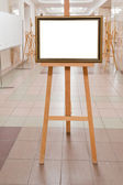 Picture frame on easel in art gallery — Stock Photo