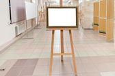 Moldura madeira dourada em cavalete no salão da galeria de arte — Fotografia Stock