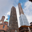 The towers and the statue under cloudy sky in Bologna - Foto Stock