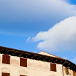 Royalty-Free Stock Photo: White clouds in blue sky under medieval house