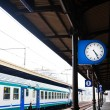 Outdoor clock on railway platform and train - Stock Photo