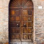 Wooden door in brick wall of medieval house — Stock Photo #17329091