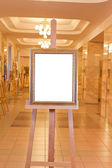 Wooden picture frame on easel in art gallery — Stock Photo