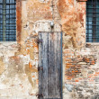 Wooden door in shabby brick wall — Stock Photo