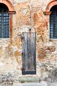 Wooden door in shabby brick wall — Stock Photo