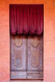 Ortaçağ evinin kırmızı perde ile ahşap kapı — Stok fotoğraf