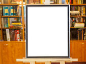 White canvas of picture frame on easel in library — Stock Photo