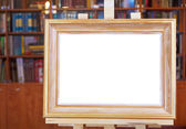 White canvas of wood picture frame on easel in library — Stock Photo