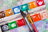 Watercolor set and brushes on oil picture background — Stock Photo