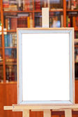 White canvas of simple picture frame on easel in library — Stock Photo