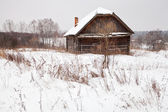 Abandoned house in snow-covered village — Stock Photo