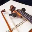 Fiddle bow and scroll on music book — Stock Photo