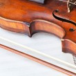 Violin sounding board and bow on music book — Stock Photo