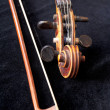 Fiddle scroll and bow on black velvet — Stock Photo