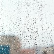Raindrops on home glass window - Stock Photo