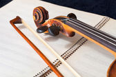 Violin bow and scroll on music book — Stock Photo