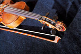 Violin pegbox and bow on black velvet background — Stock Photo
